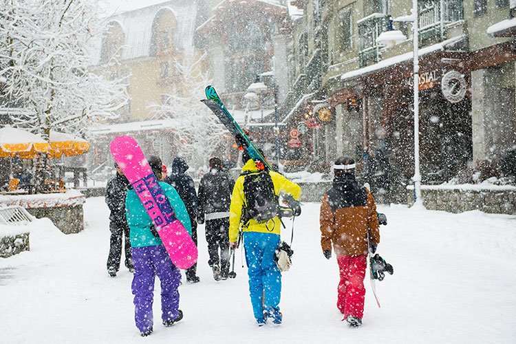 Three friends walk towards the slopes in their ski gear in Whistler.