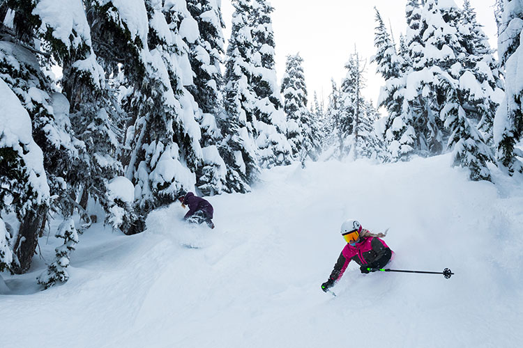 A skier and boarder power through the snow in Whistler.