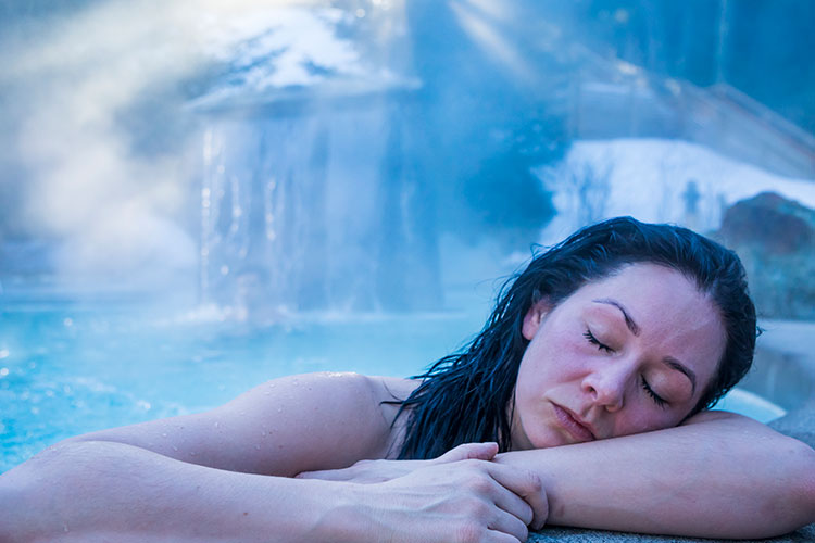 A woman enjoys the hot pool at the Scandinave Spa Whistler