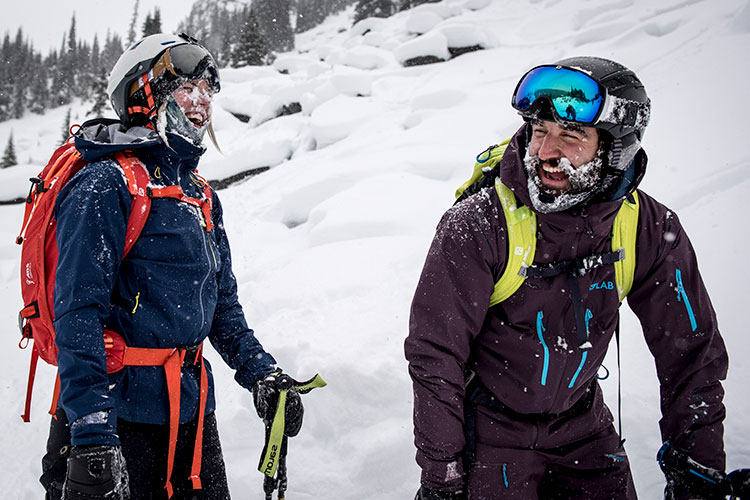 Two skiers laugh together after a powder run on Whistler Mountain.