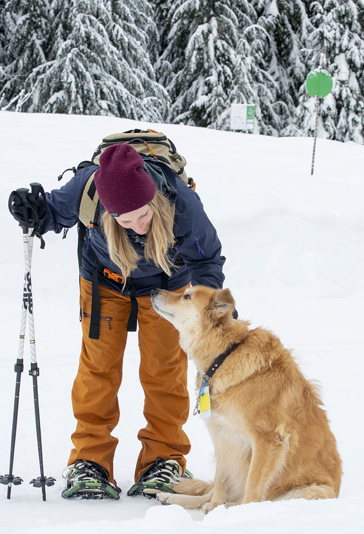 A woman pets her dog after a day spent snowshoeing at Whistler Olympic Park.