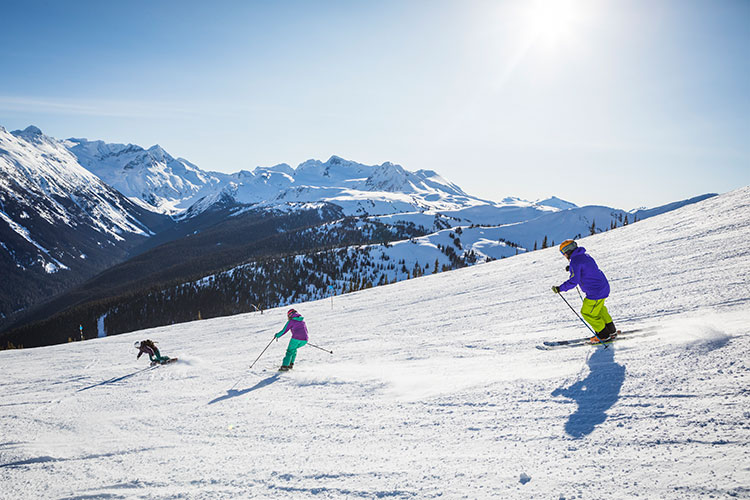 Three skiers cruise down an intermediate run on Whistler Blackcomb.