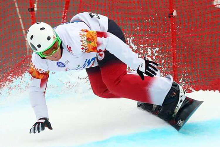 Tyler Mosher competing as a Paralympian on his snowboard