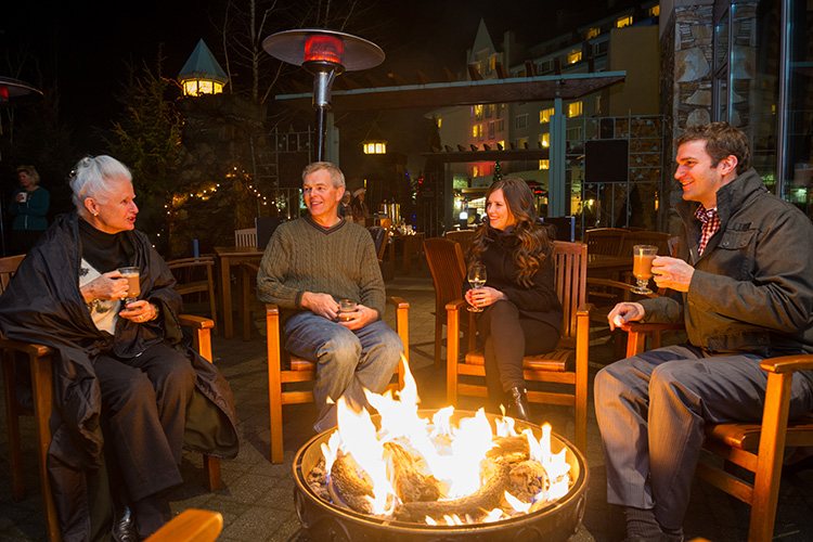 Family with drinks around a fire at Dubh Linn Gate Whistler