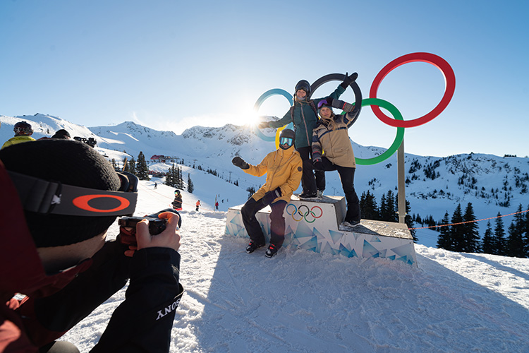 Family getting a photo taken in front of Olympic Rings in Whistler