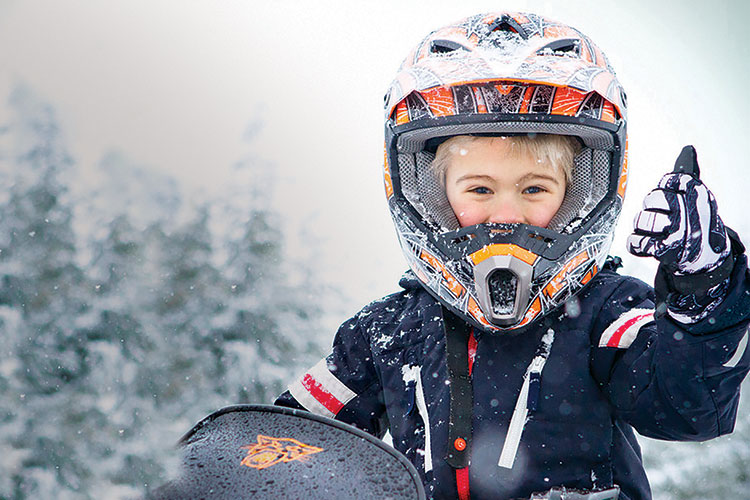 A child gives the thumbs up to the camera while snowmobiling in Whistler.