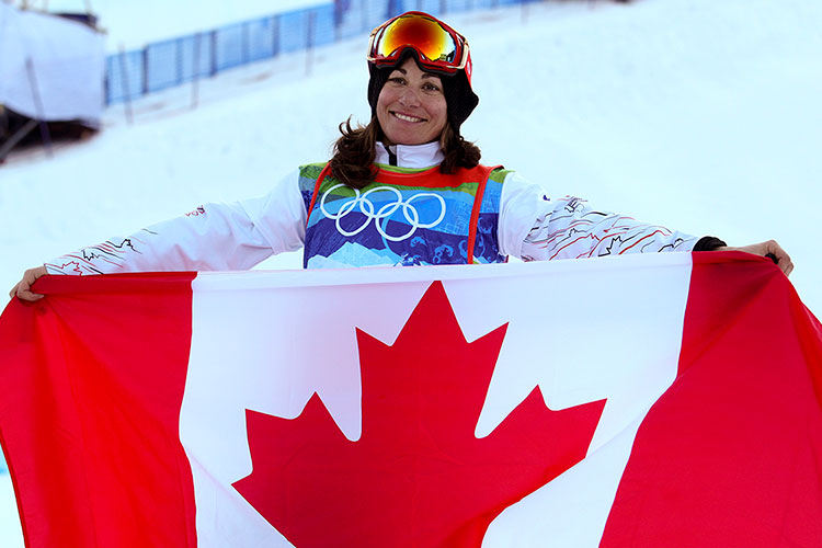 Maelle Ricker holds the Canadian flag as she celebrates her winning run at the 2010 Olympic Winter Games.