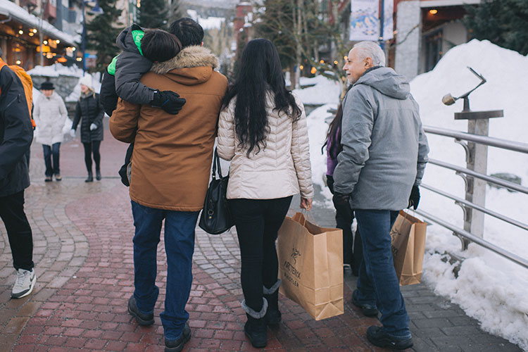 A family walk down the Whistler Village stroll while they shop.