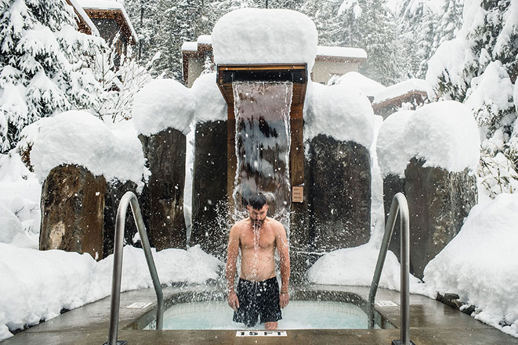 A man stands under the cold fountain at the Scandinave Spa in Whistler.