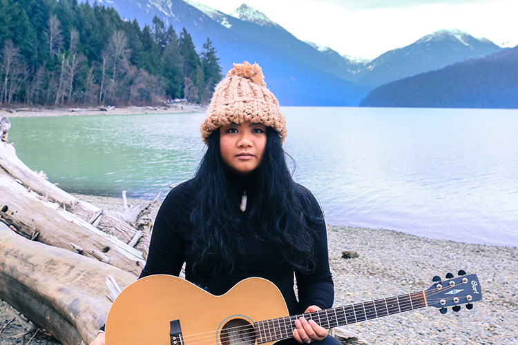 Musician Jenna Mae looks at the camera holding her guitar with a Whistler Mountain backdrop.