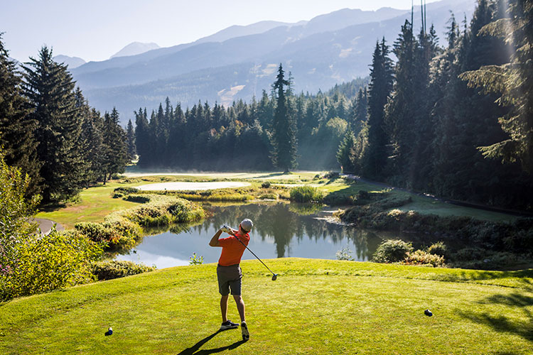 A golfer swings his club in the sunshine on a course in Whistler.