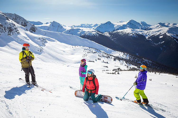 Friends gather on a ski run in the sunshine on Whistler Blackcomb.