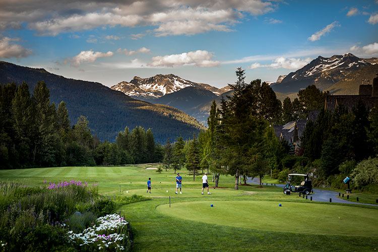 Golfers play on a Whistler golf course in the shadow of the mountains.