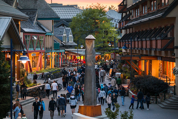 Crowds in Whistler Village walk down the stroll in the alpen glow.