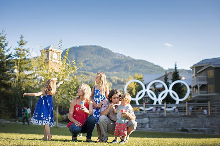 A family blow bubbles on a sunny day in Whistler Olympic Plaza.