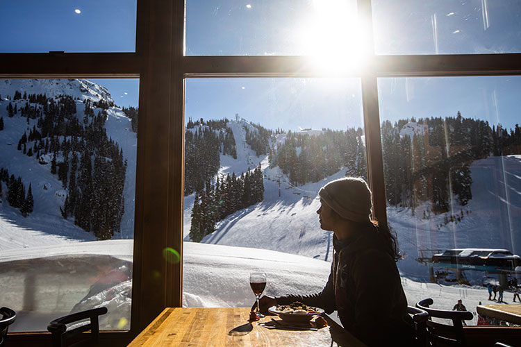 A woman enjoys the mountain views over lunch at Whistler Blackcomb.