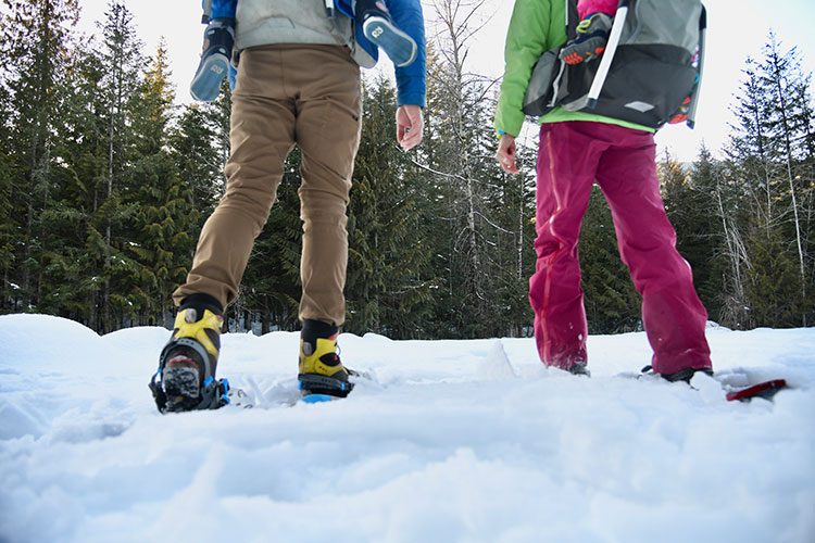 Four sets of legs, two dangle from backpacks. Parents are taking their children on a snowshoe adventure in Whistler.