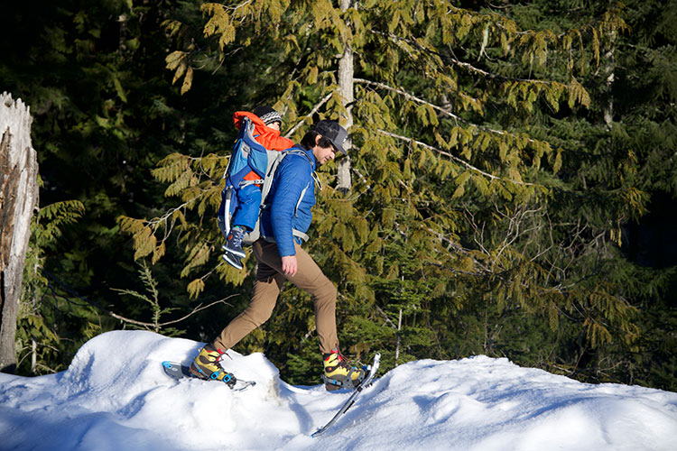 A father carries his son in a backpack as he snowshoes at Whistler Olympic Park.