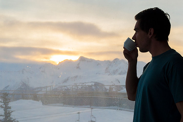 A man drinks coffee at the Roundhouse Lodge on Whistler Mountain overlooking the mountains at sunrise.