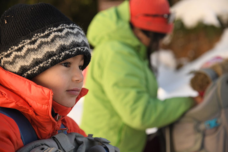 A toddler waits in a backpack to go on a snowshoe trip in Whistler.