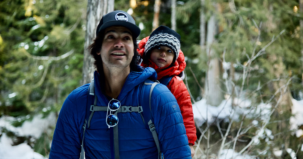 A father snowshoes with his young son in a backpack in the old-growth forest of Whistler Olympic Park.