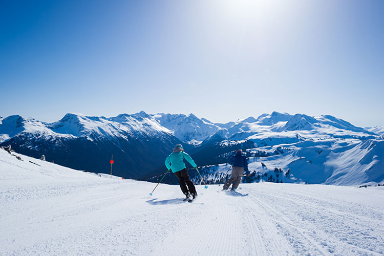 Two skiers in the sunshine on the Dave Murray Downhill run on Whistler Blackcomb.