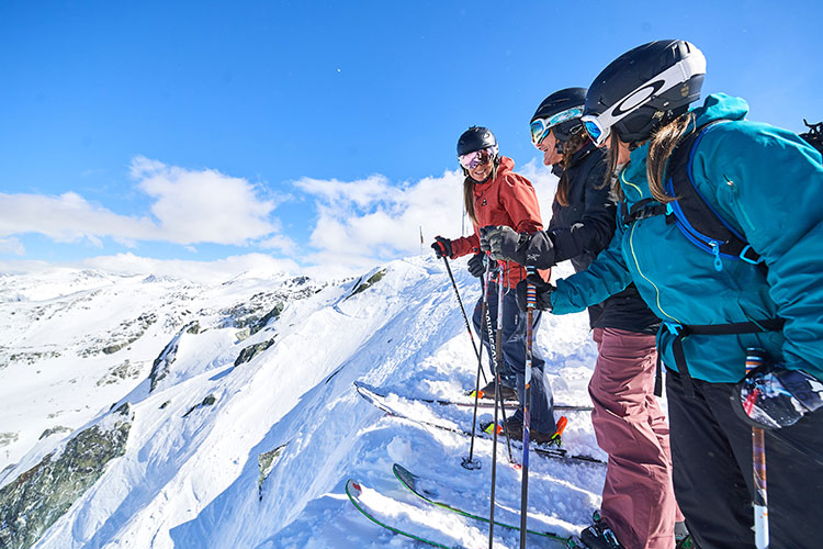 Three skiers consider the drop-in on Spanky's Ladder on Whistler Blackcomb.