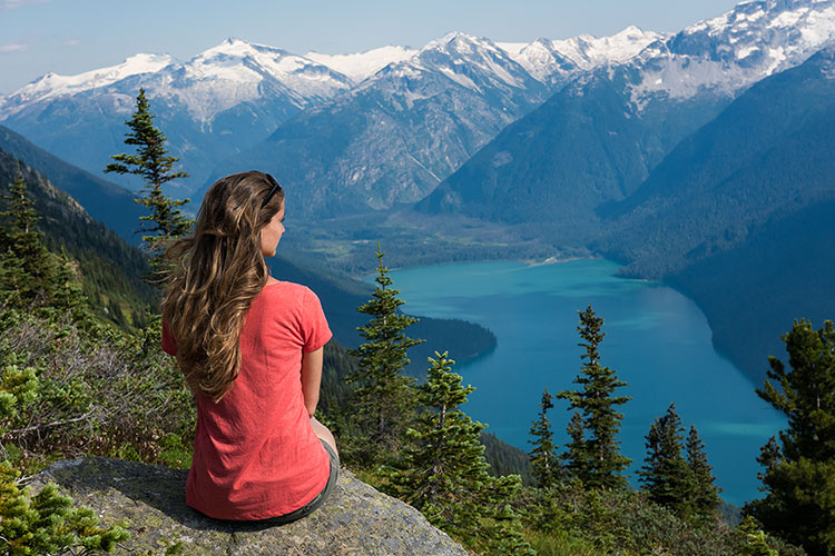 A woman enjoys the mountain views on a hike in Whistler.