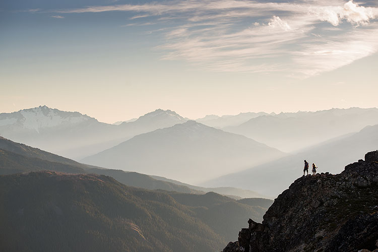 A couple hike high on the mountains in Whistler with the Coastal Mountain Range in the background.