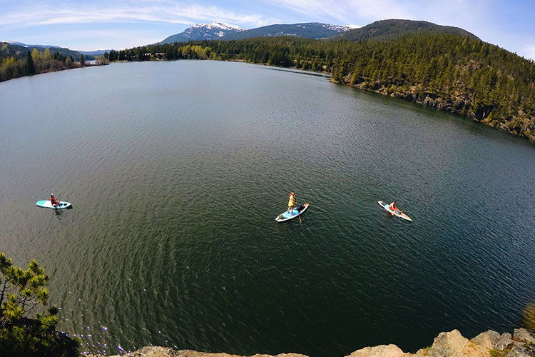 Paddle boarders enjoy the summer sun on Green Lake in Whistler.
