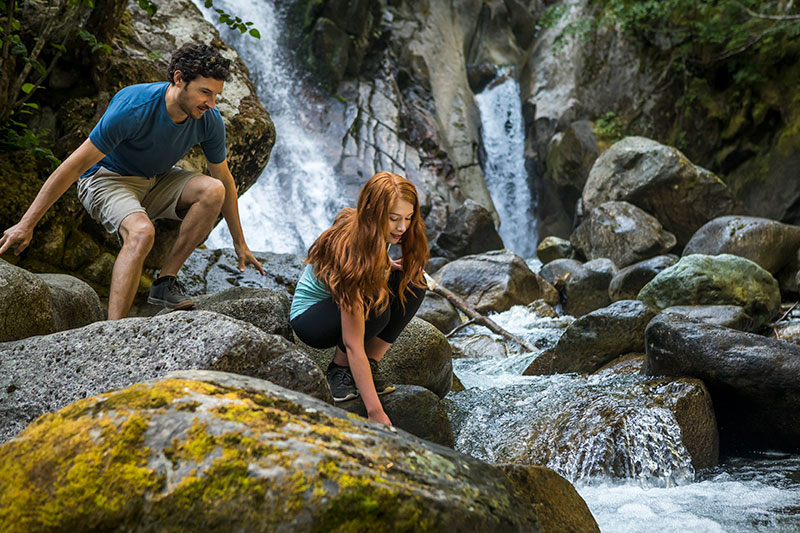 A couple explores the base of a waterfall in Whistler.