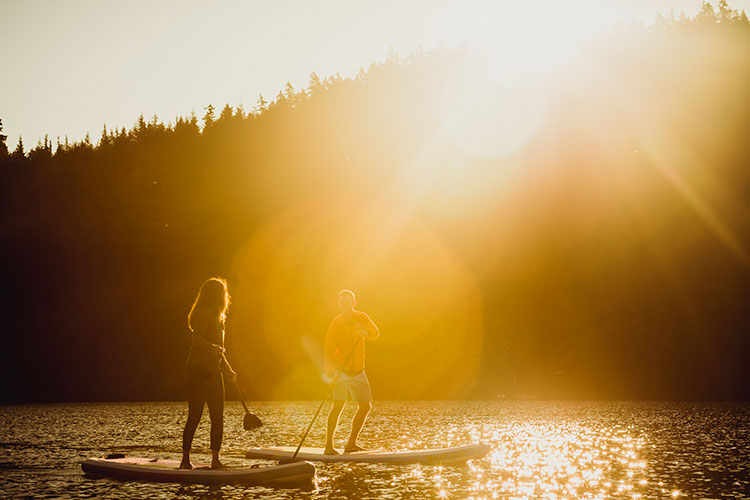 A couple stand up paddle board at sunrise on a lake in Whistler.