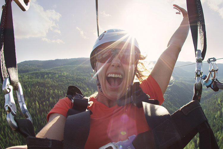 A woman's face smiling as she zips across the valley with Superfly Ziplines in Whistler.