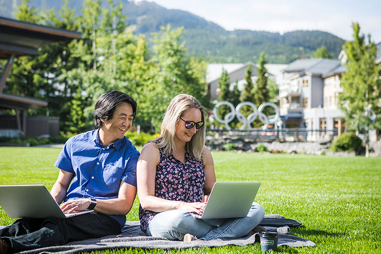 A man and woman sit in Whistler Olympic Plaza working on their laptops.