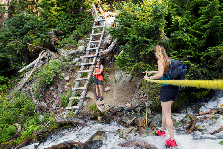 Two women cross a bridge in the Callaghan Valley.
