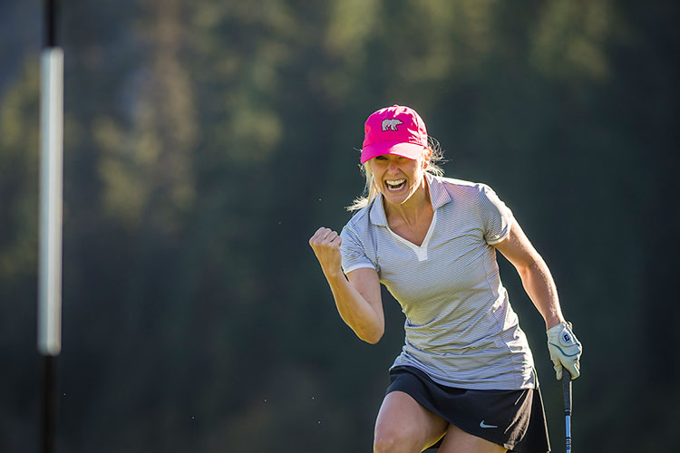 A woman pumps her fist after a hole in one on a golf course in Whistler.