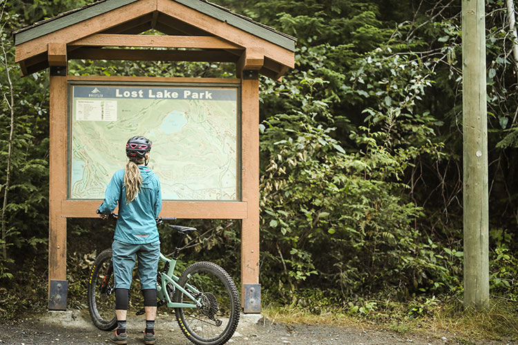 A mountain bikers examines a trail map at Lost Lake Park in Whistler.