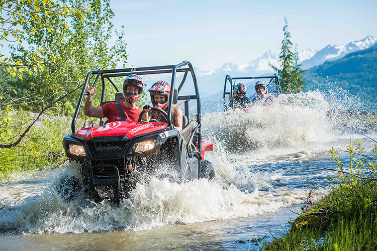 Two mountain buggies splash through water in Whistler.