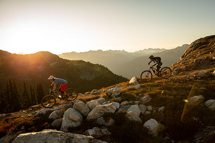 Two mountain bike riders comes down the trail as the sun sets in Whistler.