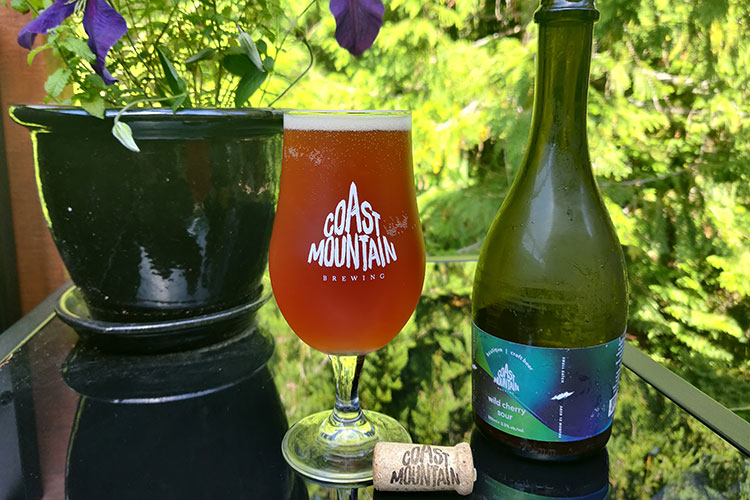A glass of the Coast Mountain Wild Sour Cherry beer sits on an outdoor table.