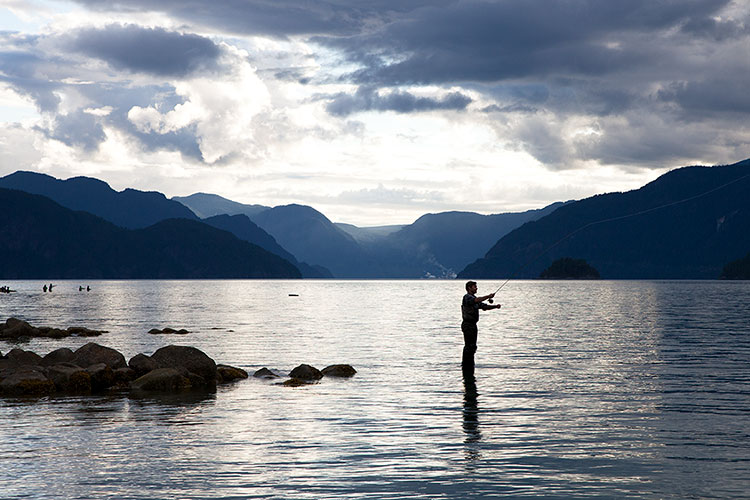 A fisherman casts in the early morning light in Squamish.