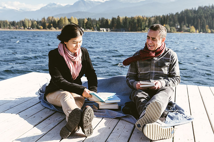 A man and a woman sit on a dock on Alta Lake in Whistler reading and discussing books.