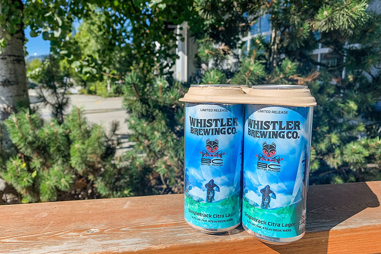 A six pack of Whistler Brewing Company lager on a bench in the sunshine.