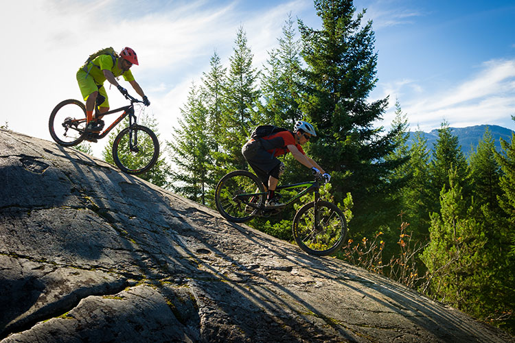 Two cyclists tackle a rock roll in Whistler.