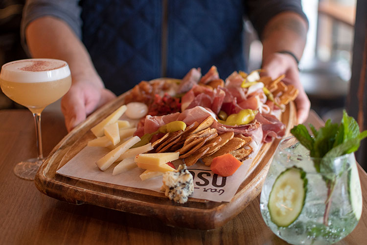 A man holds a charcuterie board filled with meats, cheese, chutneys and crackers in between two cocktails at Bar Oso in Whistler.