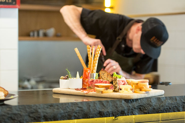 A chef works in the background with a freshly prepared charcuterie board set on the table in the foreground.