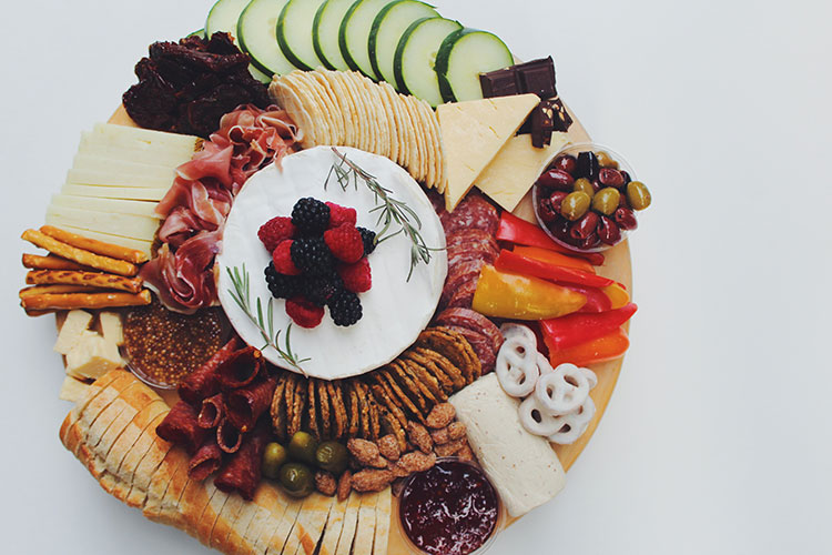 A round charcuterie platter with cheeses, crackers, veggies, olives, meats and sweet treats.