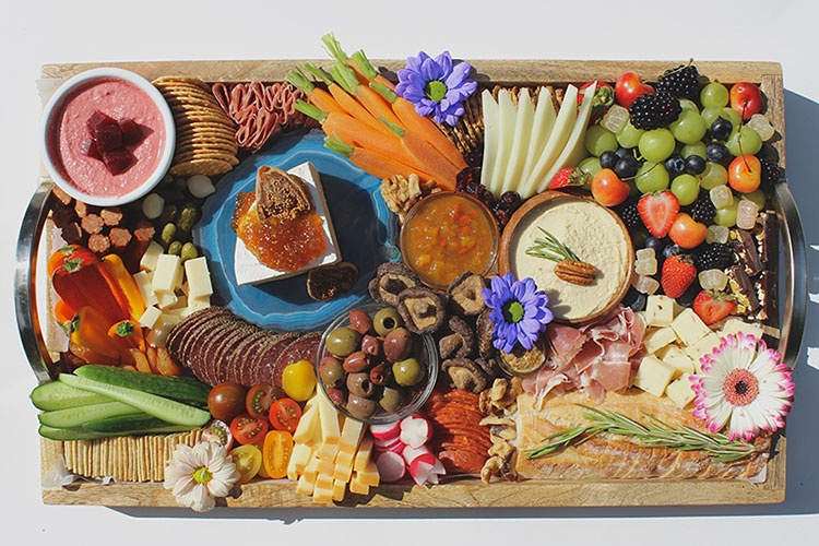 A colourful charcuterie platter with meats, cheeses, flowers, berries, chutneys and sauces.