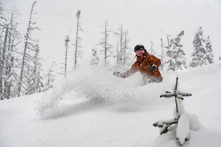 A snowboarder ploughs through powder on the slopes in Whistler.