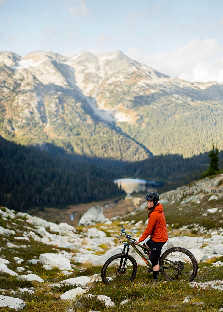 A mountain biker looks out at the view on the Lord of the Squirrels Trail in Whistler.